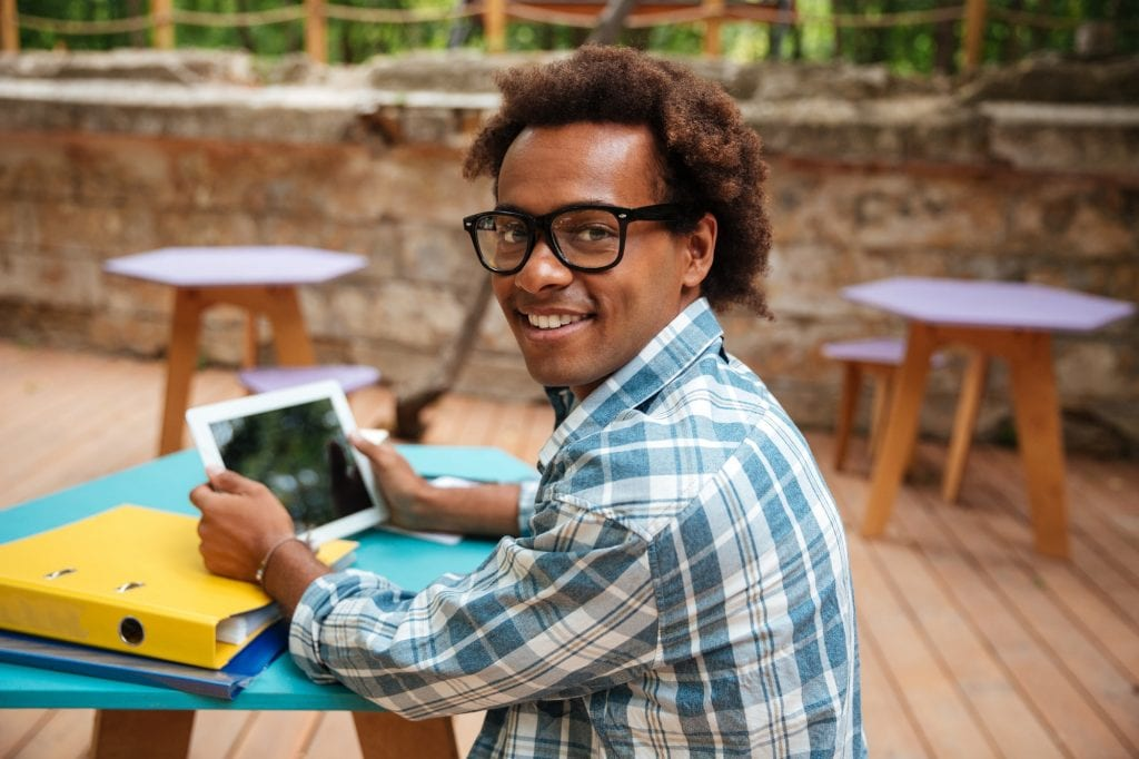 Cheerful african young man in glasses smiling and using tablet